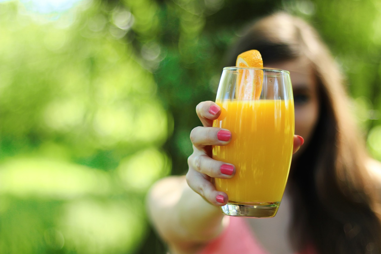 Chica con un vaso de zumo de naranja en la mano