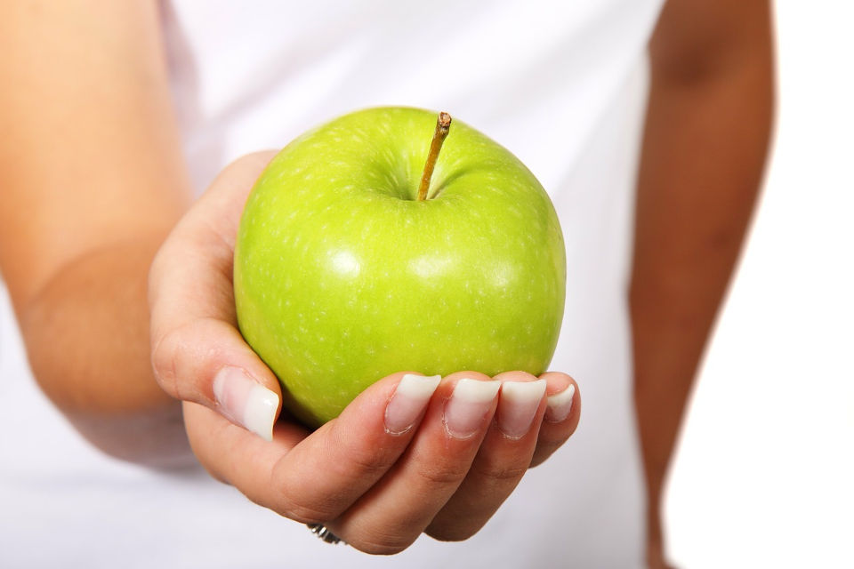 Mujer ofreciendo una manzana