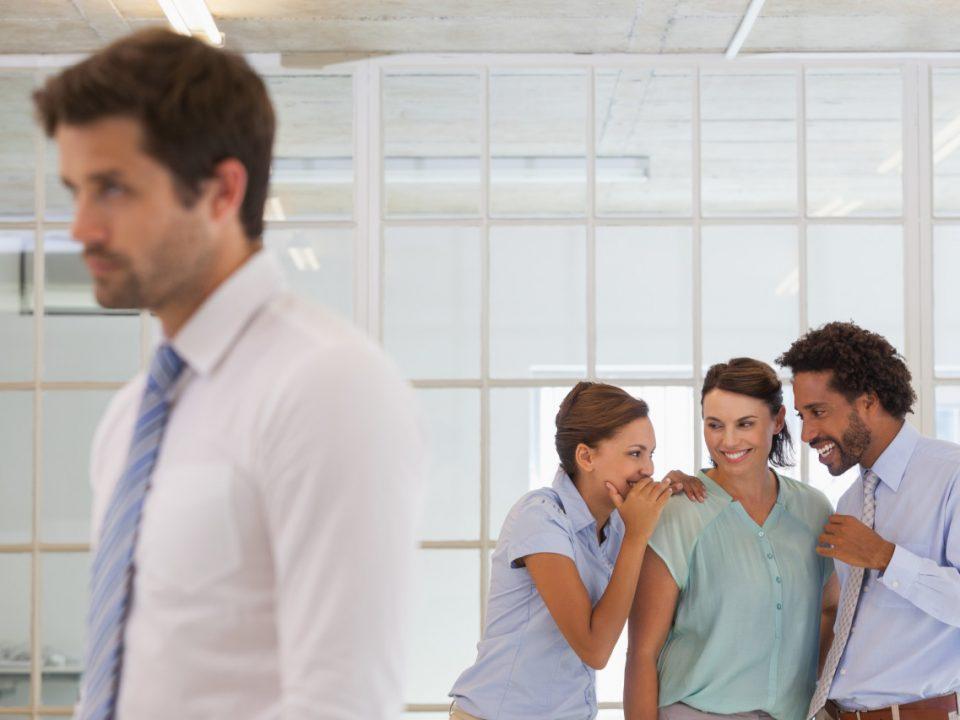 Grupo de empleados haciendo comentarios a espaldas de otro