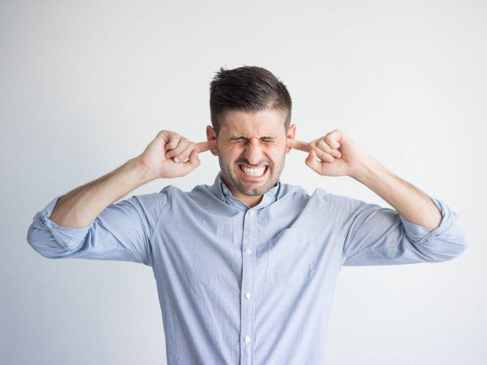 Hombre tapándose los oídos