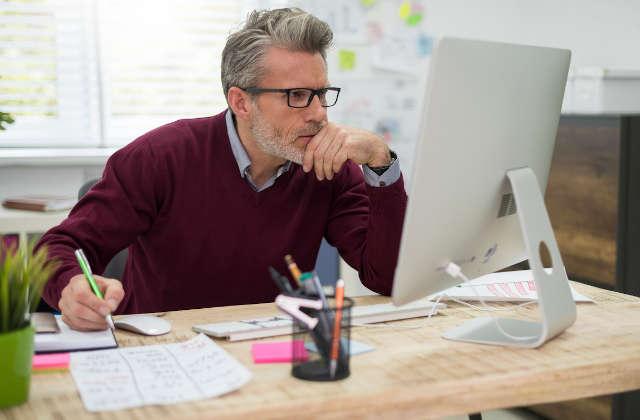 Hombre pensativo trabajando en el ordenador